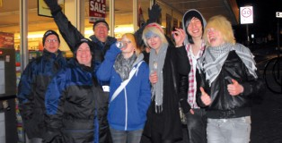 Young revellers in Hastings flanked by three street pastors (left)