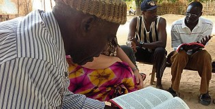 A new believer reading his Bible in his own language