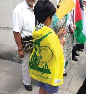 Peaceful demonstration? A child wrapped in a Hezbollah flag with assualt rifle image clearly visible Picture: Christians United for Israel