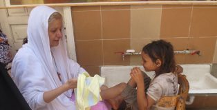 The Egyptian Mother Teresa: Mama Maggie washes a Christian child's feet