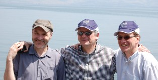 "Roger Greene, left, with fellow directors Simon Thane (centre) and Alastair Mitchell-Baker on the shore of the Church of St Peter's Primacy, purportedly where Jesus told his disciples to ""let down their nets on the othe4r side"""