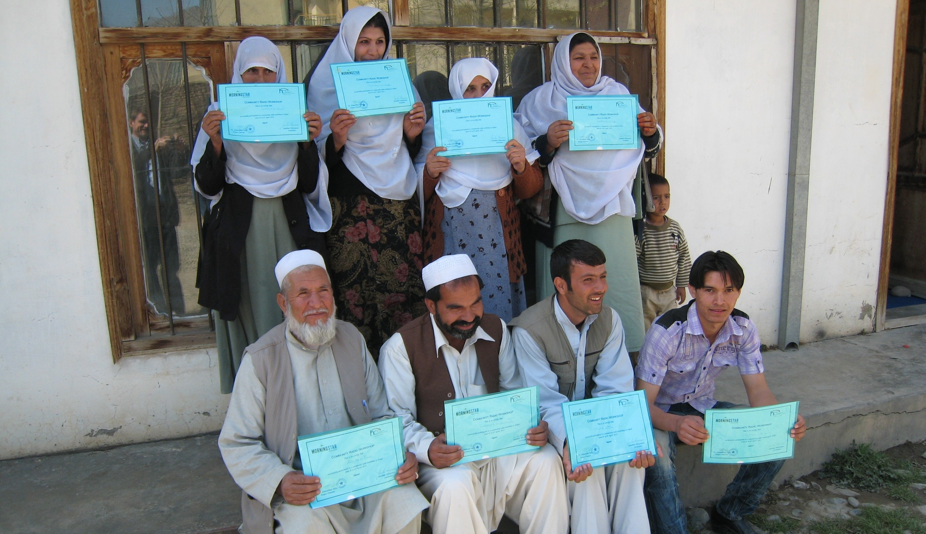 Afghan community health workers proudly displaying their certificates in Community Media after an HCR workshop