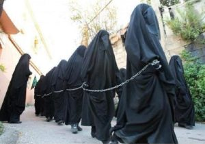 Captured Christian and Yazidi women are chained and forced to wear full Islamic dress
