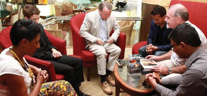 Lord David Alton (centre) praying for the situation facing Pakistani Christians in Thailand with Wilson Chowdhry (right), founder of the British Pakistan Christian Association, Rev Tim Eaddy of Christchurch Anglican Church in Bangkok and local Christians