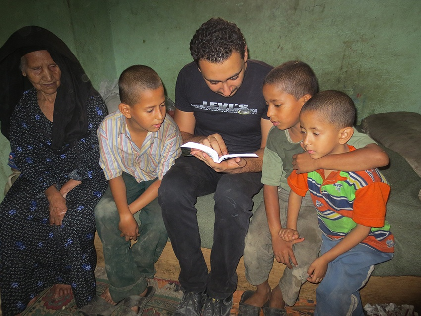 A Stephen's Children worker reads the Bible with a poor Christian child as part of the weekly home visiting programme