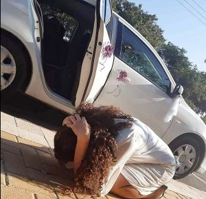 woman crouches next to her car during a rocket attack